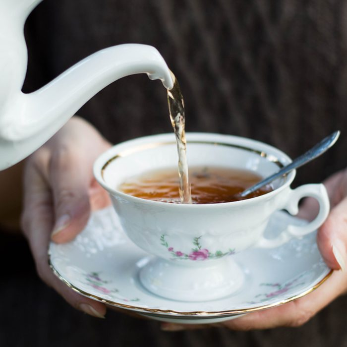 Closeup shot from hands holding a teacup and pouring tea