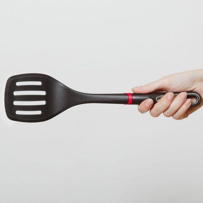 Close up of female hand horizontal holding black spatula isolated on white background.