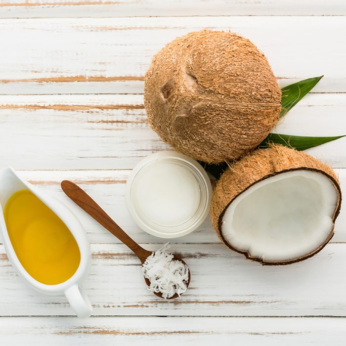 Coconut with coconut oil on white wooden table background.