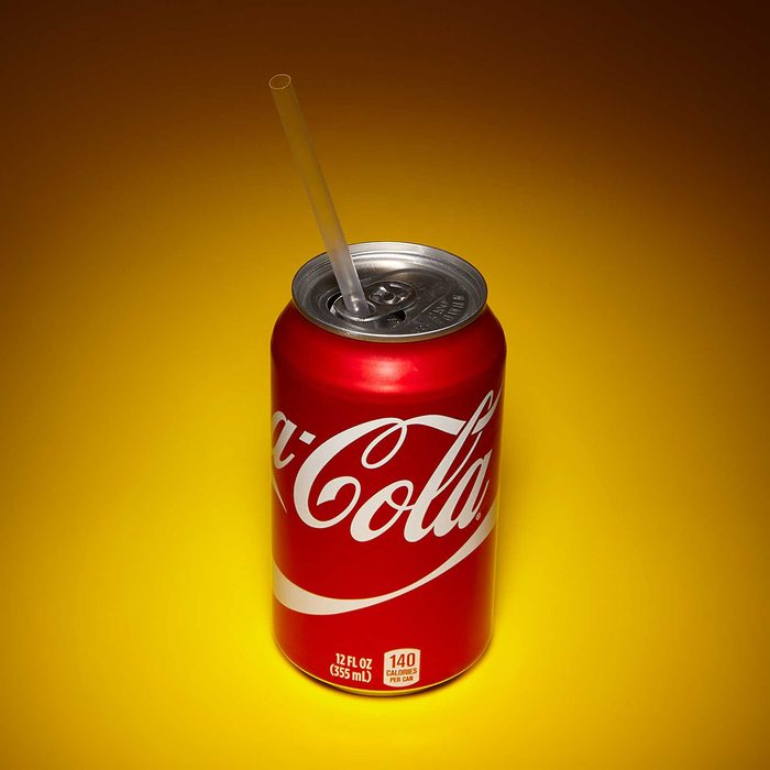 Soda can with straw held in place by the tab