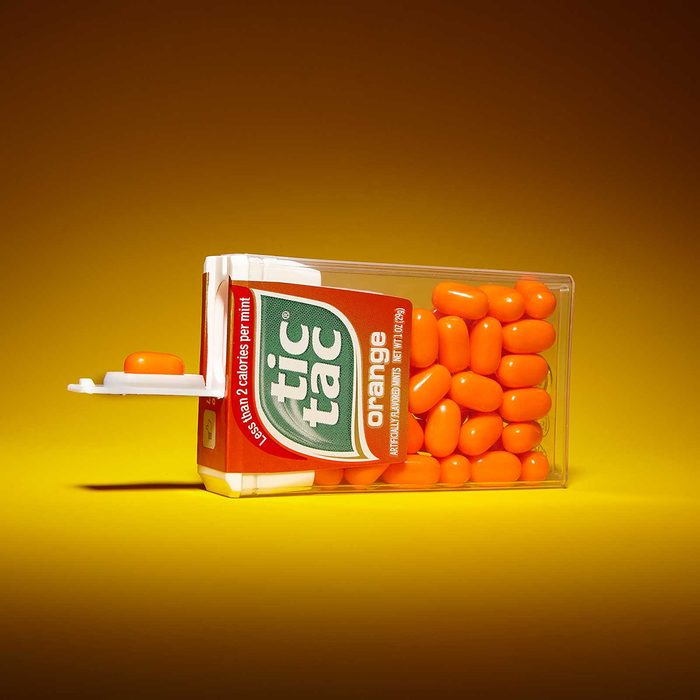Tic tac container on its side with one candy held out in its lid