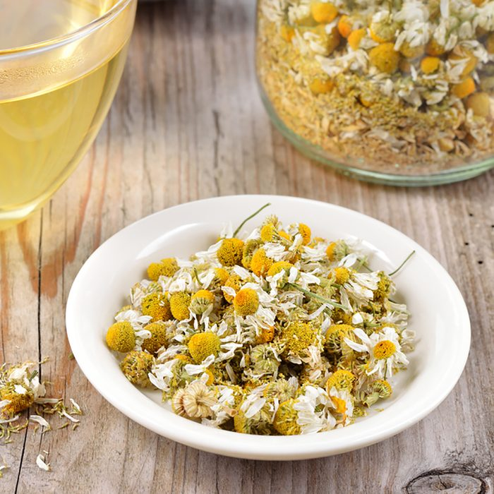 Dried camomile flowers on saucer. Chamomile tea in a transparent cup and dried camomile flowers on wooden table. Herbal tea for baby's stomach.; Shutterstock ID 222521101