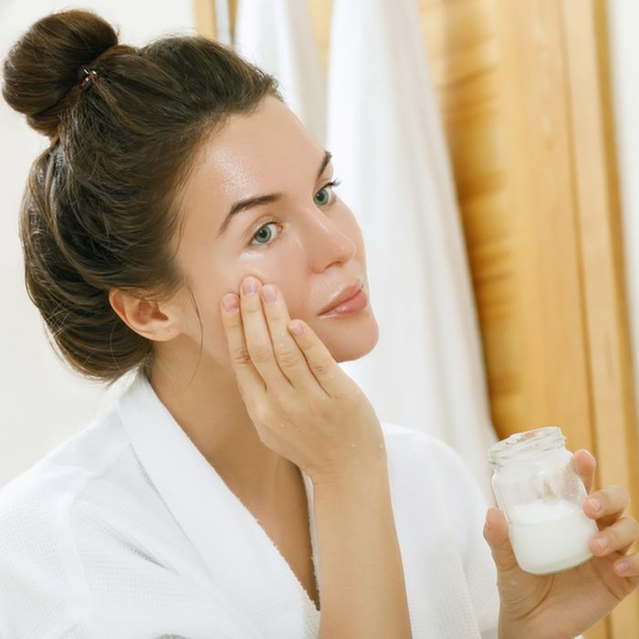 Woman is moisturizing her skin with a coconut oil