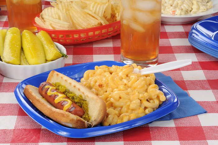A grilled hot dog with macaroni and cheese on a picnic table; Shutterstock ID 104089265