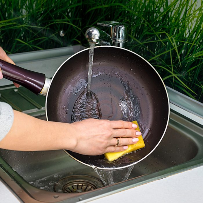 Female hand washing frying pan close up under running water, Young housewife woman washing griddle in a kitchen sink with a yellow sponge, Hand cleaning, manually, by hand, housework dishwasher,; Shutterstock ID 1079775416; Job (TFH, TOH, RD, BNB, CWM, CM): TOH