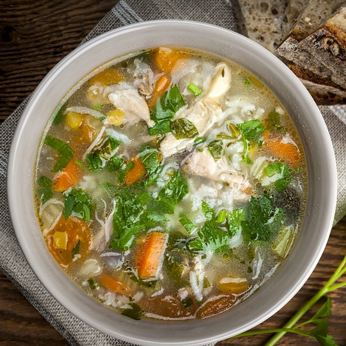 Chicken rice soup with vegetables in bowl and bread from above
