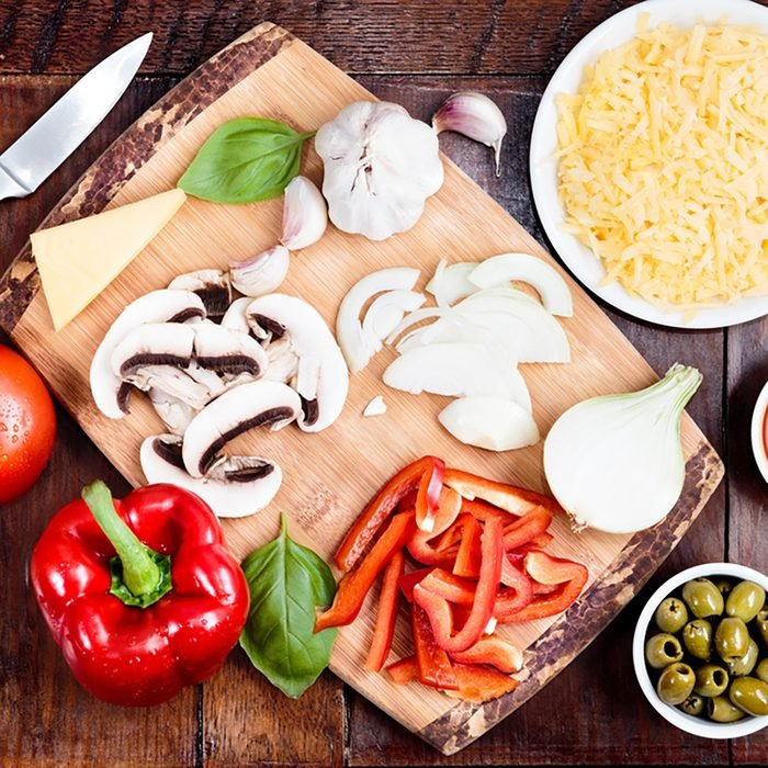 Fresh ingredients for homemade pizza on wooden table