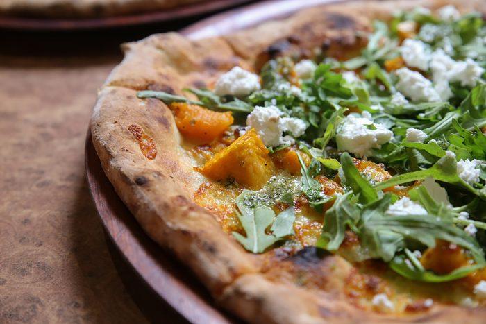 wood fired pumpkin feta rocket pizza on wooden plate