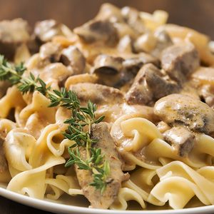 Selective focus was used on this close-up image of creamy beef stroganoff made with egg noodles, beef, mushrooms and garnished with fresh rosemary