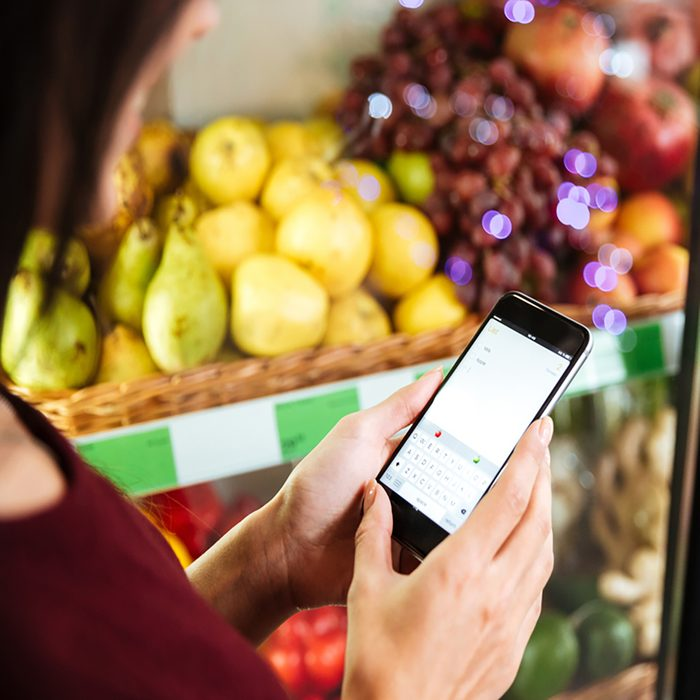 Closeup of woman using cell phone in grocery store