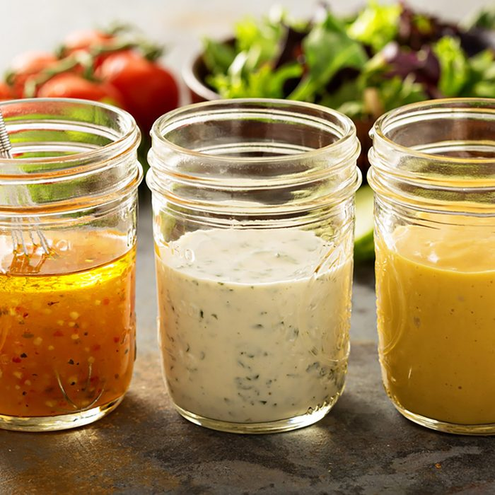 Variety of homemade sauces and salad dressings in mason jars including vinaigrette, ranch and honey mustard