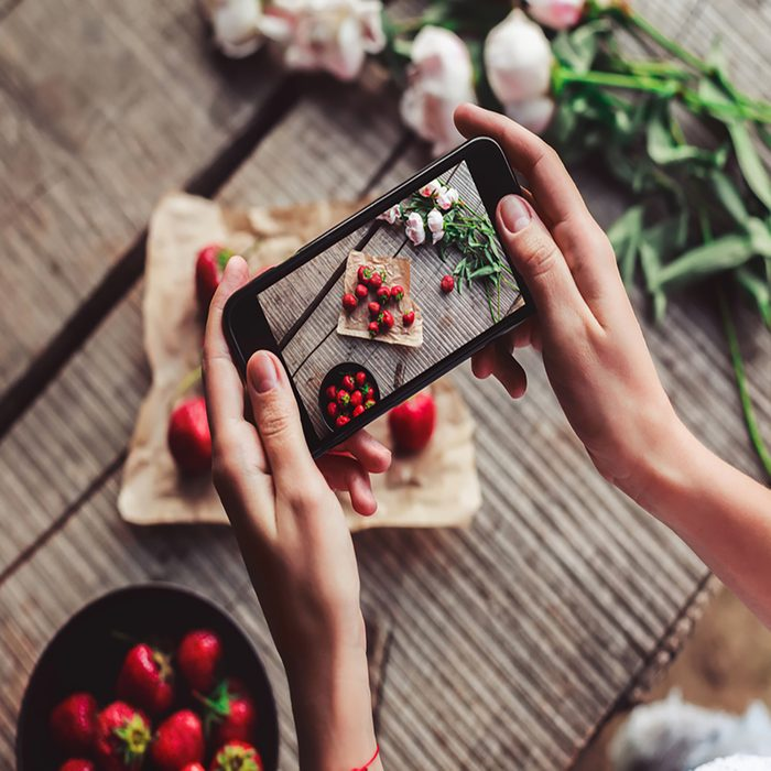 Girl's hands taking photo of breakfast with strawberries by smartphone. Healthy breakfast, Clean eating, vegan food concept.