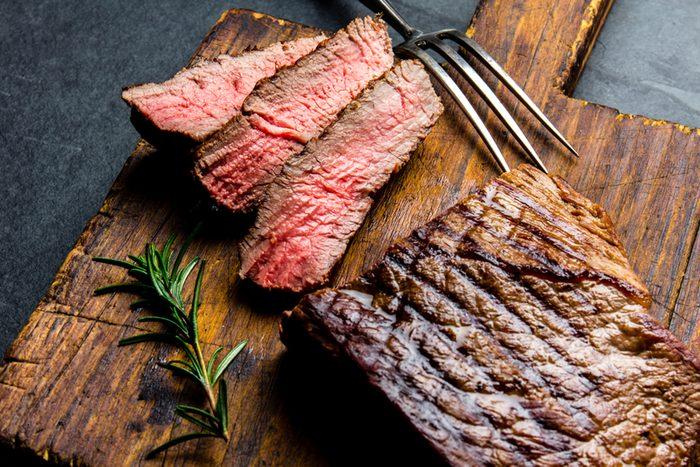Sliced grilled medium rare beef steak served on wooden board