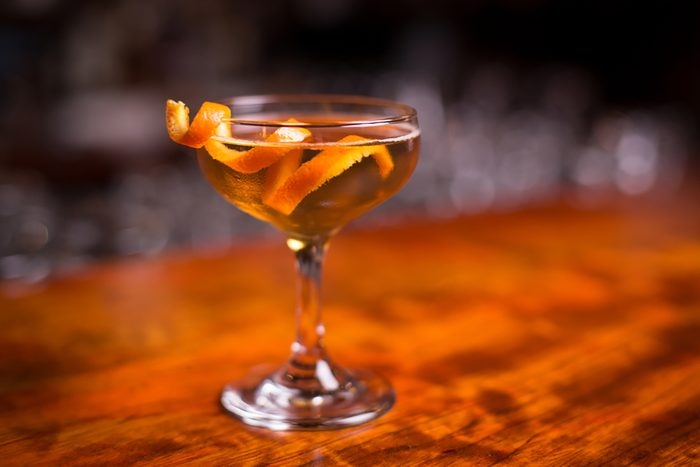 Low angle closeup of gourmet old fashion martini drink in champagne saucer cocktail glass filled with bourbon and brandy garnished by delicately spiral orange peel on red cherry wood grain countertop.