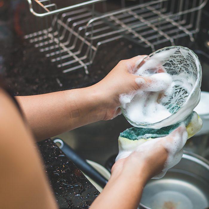 A woman washing bowl glass by dish soap make many bubble