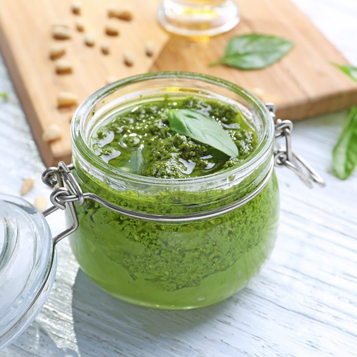 Jar with delicious basil pesto sauce on table