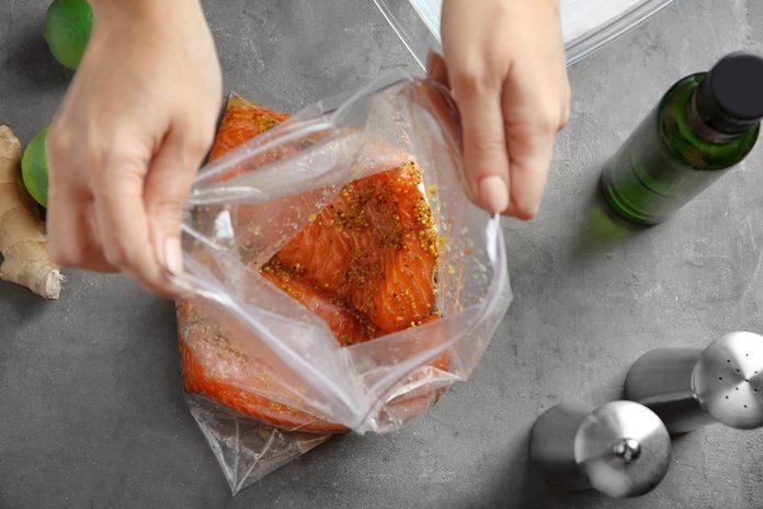 Woman preparing salmon fillet with honey mustard marinade in zip lock bag on table