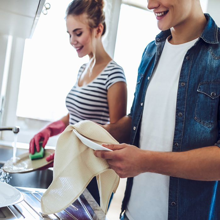 Cropped image of young happy couple is washing dishes while doing cleaning at home.
