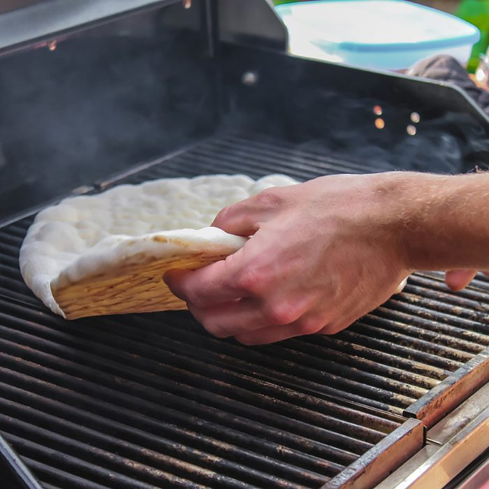 Hand flipping flatbread cooking on outside electric grill showing browned bottom and top not yet cooked