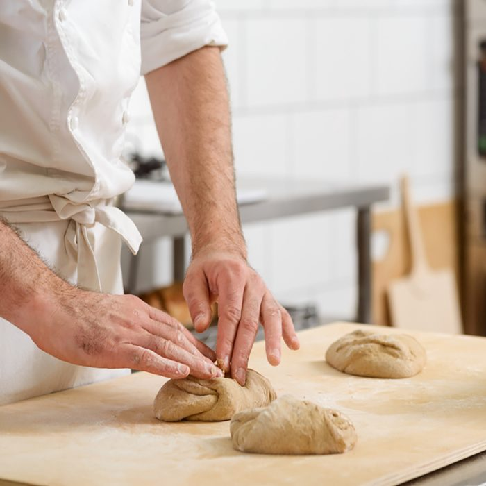 Baker is kneading dough made of whole wheat flour and forming loaves. Cooking bread for selling in the bakery store.