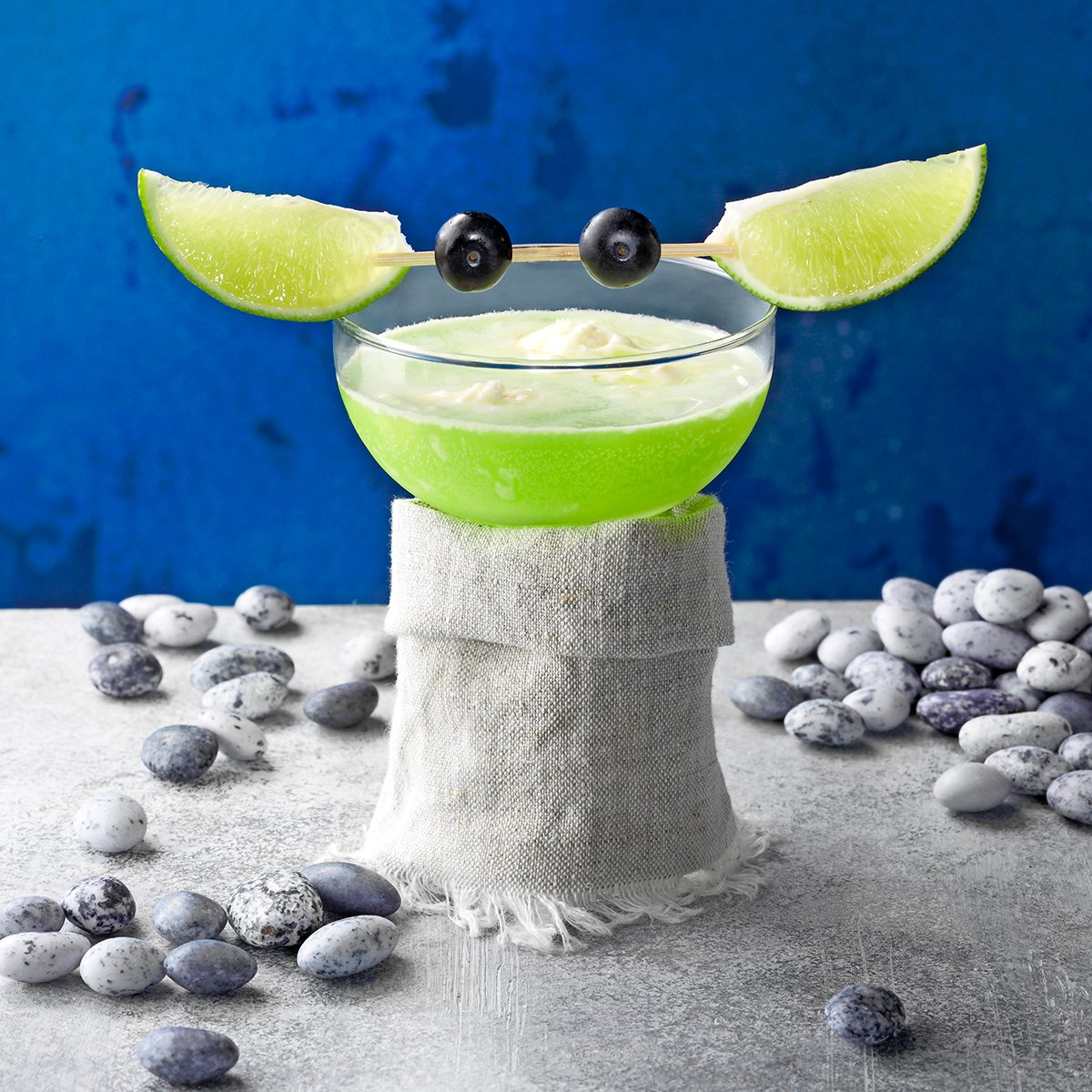 Yoda Soda; grey surface; gray surface; blue background; copy space; low camera angle; star wars; rock candy; blueberries; limes; lime wedges; grey; cloth; gray cloth; fantasy