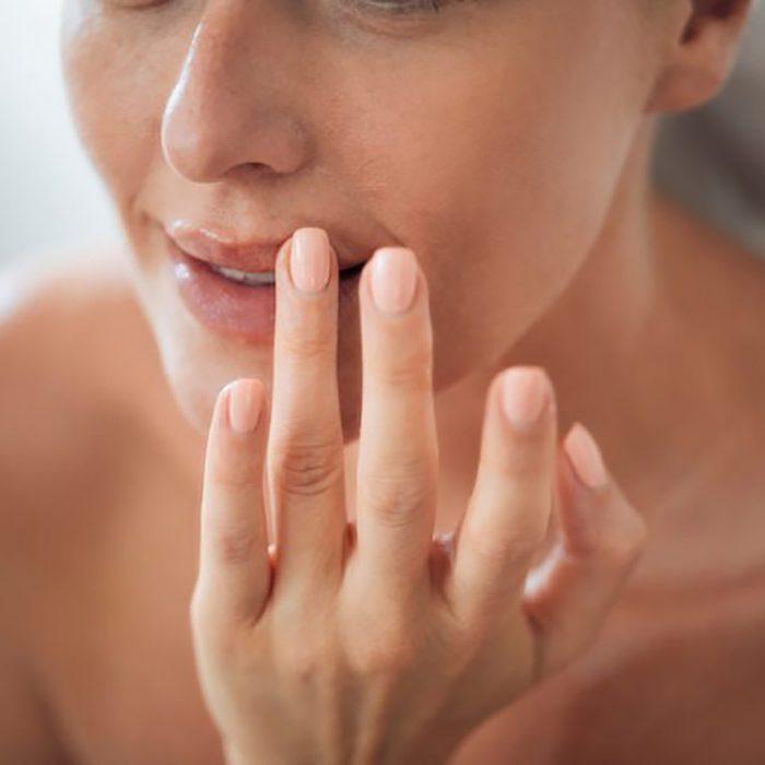 woman touching her lip