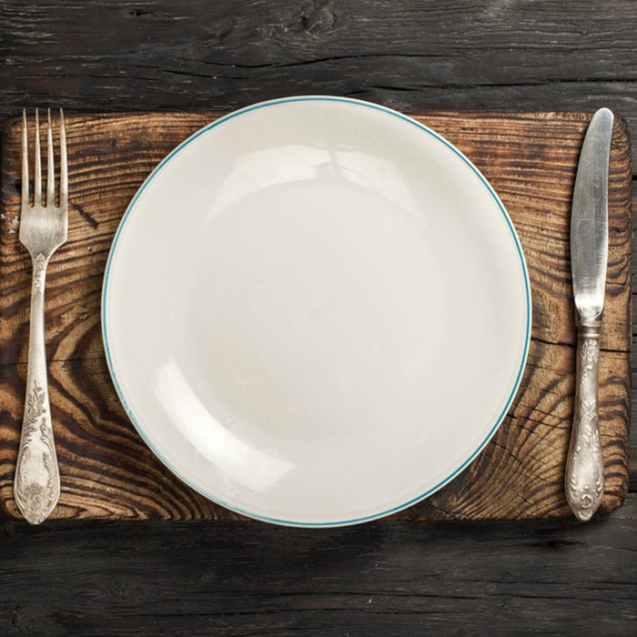 White empty plate with fork and knife on a old wooden board on a dark wooden background