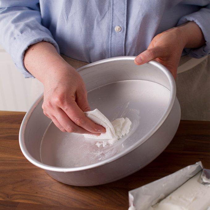 greasing a cake pan