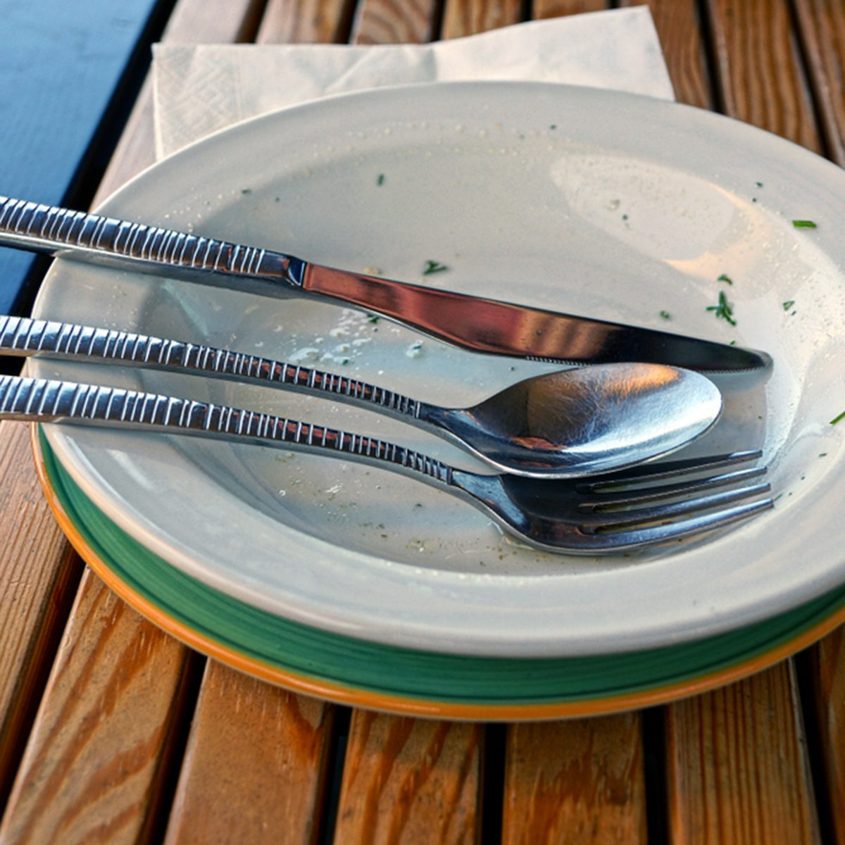 Dirty dishes with cutlery on a brown wooden table