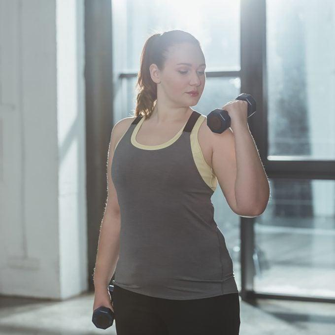 Curvy girl lifting dumbbells in gym