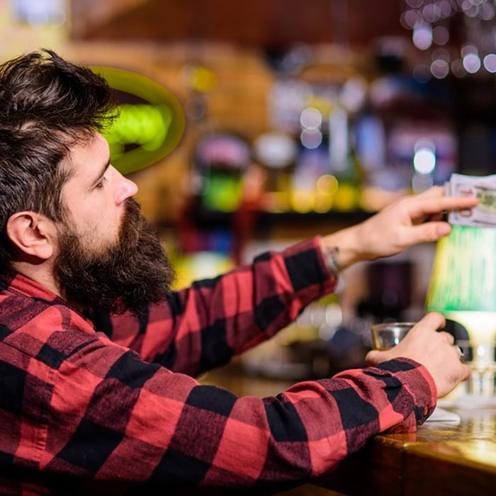Man with drunk face sit alone at bar counter. Hipster holds glass with alcoholic drink and money, ordering more drinks.