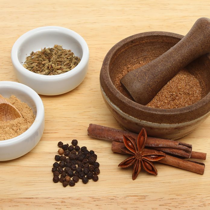 Ingredients for Chinese five spice with ramekins and a pestle and mortar on a wooden board