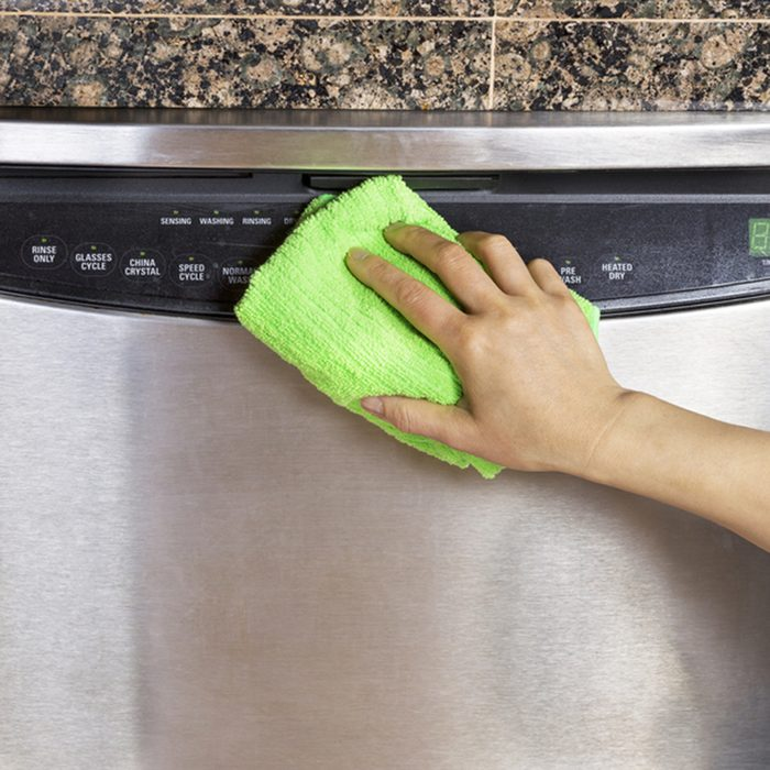 Female hand wiping down front part of stainless steel dishwasher with microfiber towel
