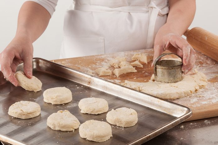 Young woman with lovely hands making home-made buttermilk biscuits using fresh ingredients