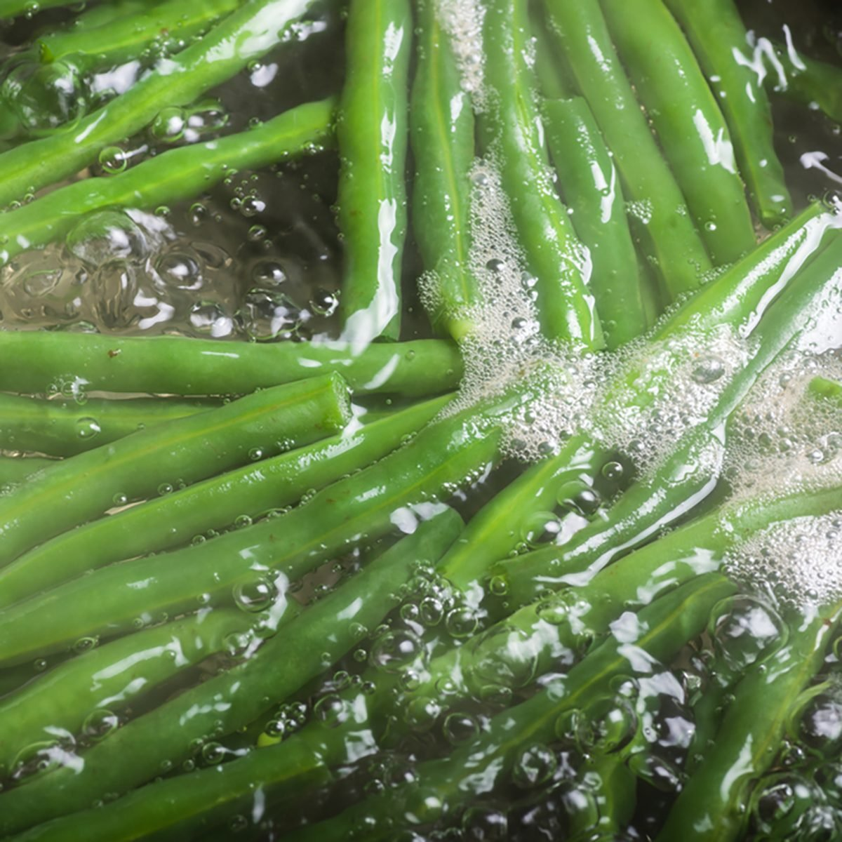 Fresh green beans boiling in water on stove