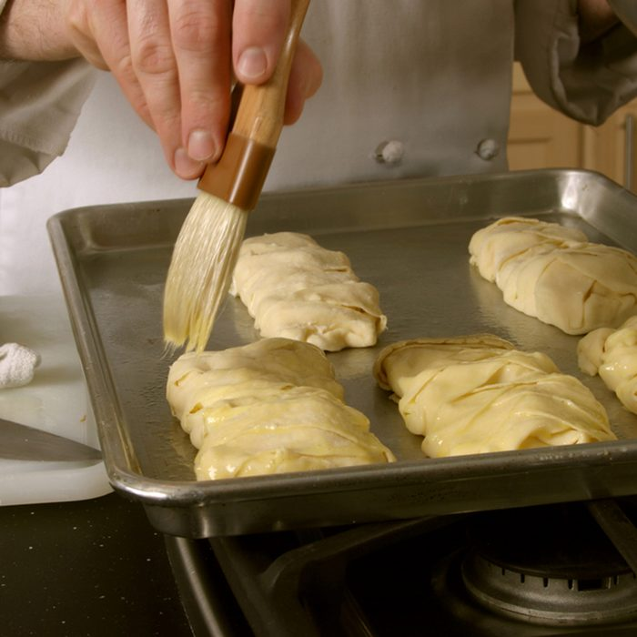 A chef prepares stuffed pastries by brushing egg over the top before baking