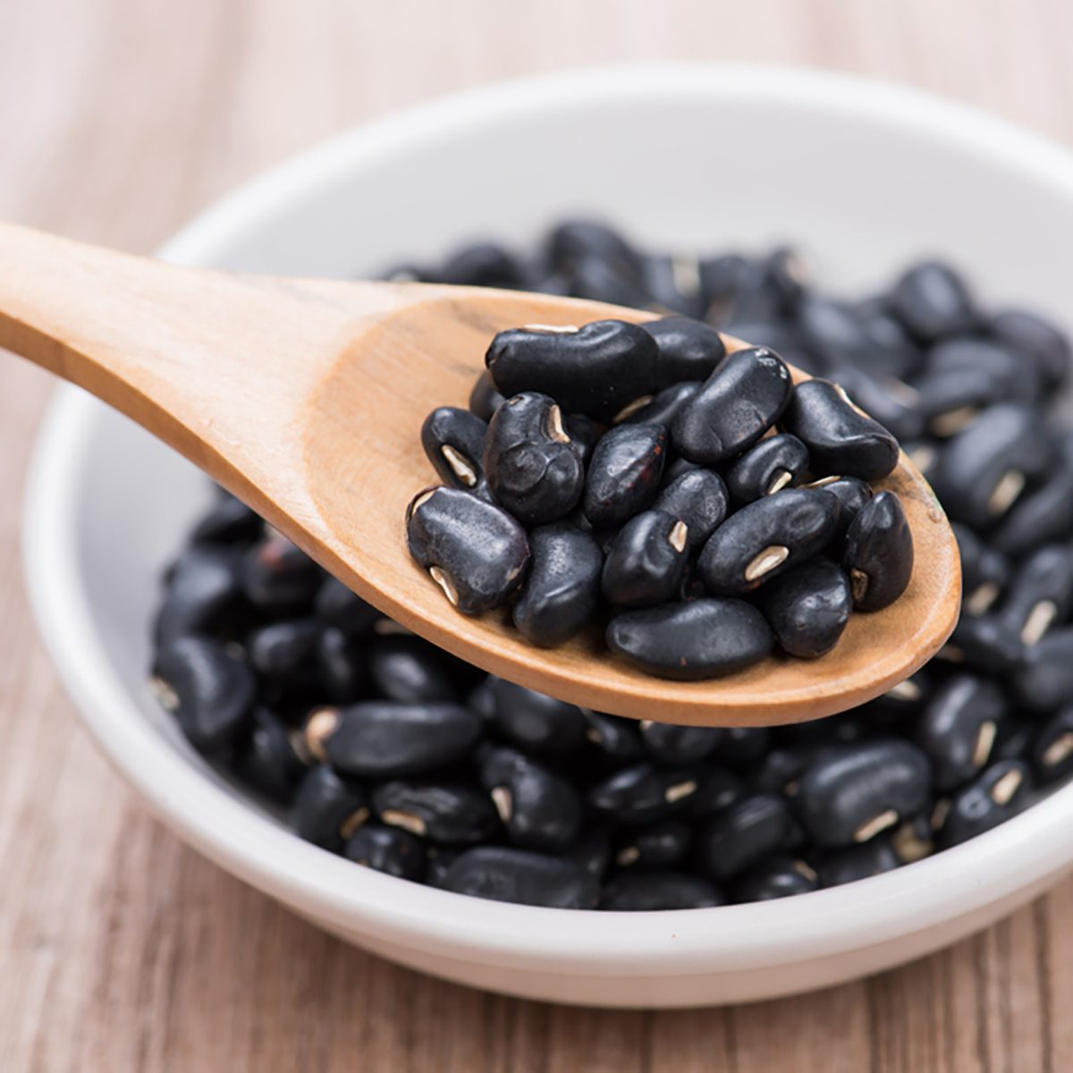 Black Beans in wooden spoon with ceramic bowl
