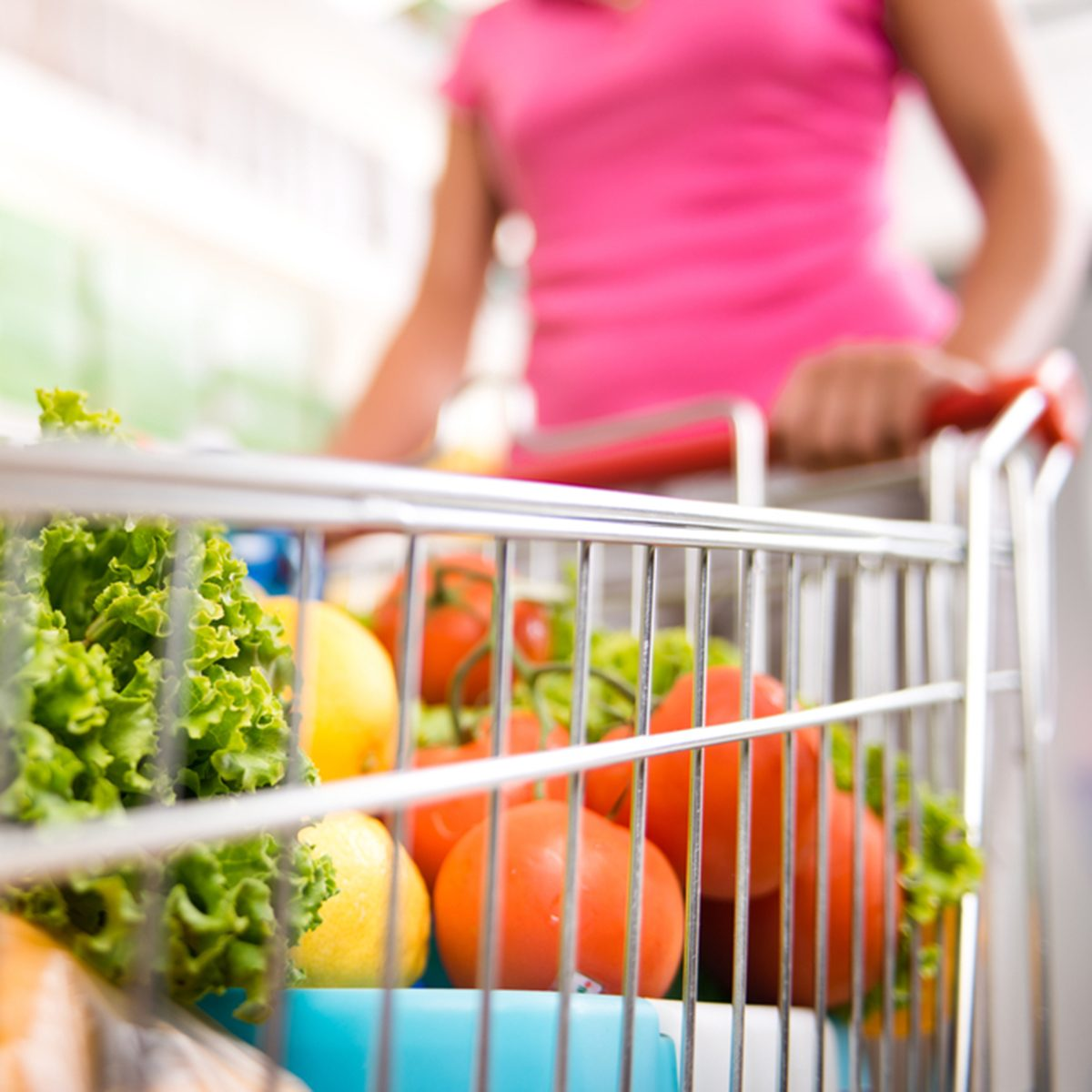 Woman at supermarket pushing a shopping cart filled with fresh fruit and vegetables.