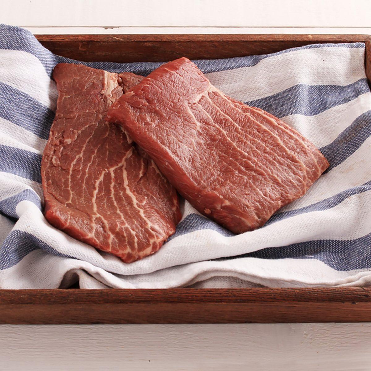 fresh flat pan beef steak in wooden tray