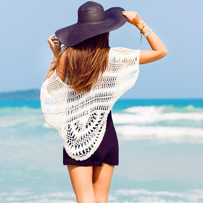 Outdoor summer portrait of young pretty woman looking to the ocean at tropical beach, enjoy her freedom and fresh air, wearing stylish hat and clothes