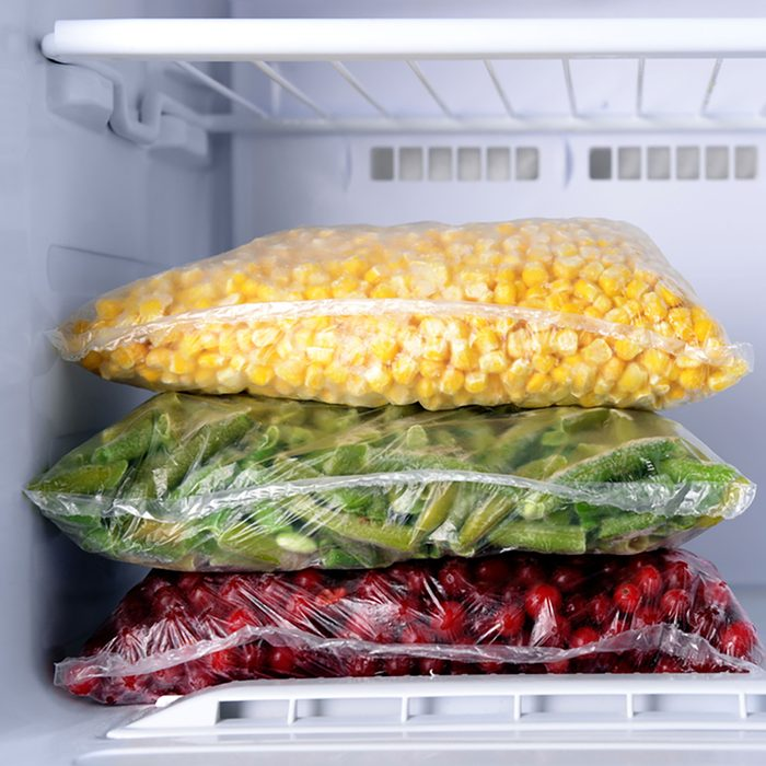 Frozen berries and vegetables in bags in freezer close up;