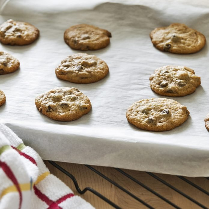 Hot freshly baked chocolate chip cookies are cooling on a parchment paper lined baking sheet.