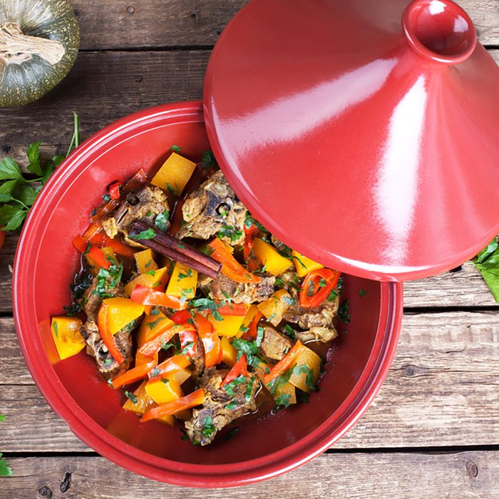 Moroccan Tagine with lamb, pumpkin and red pepper on a wooden table.