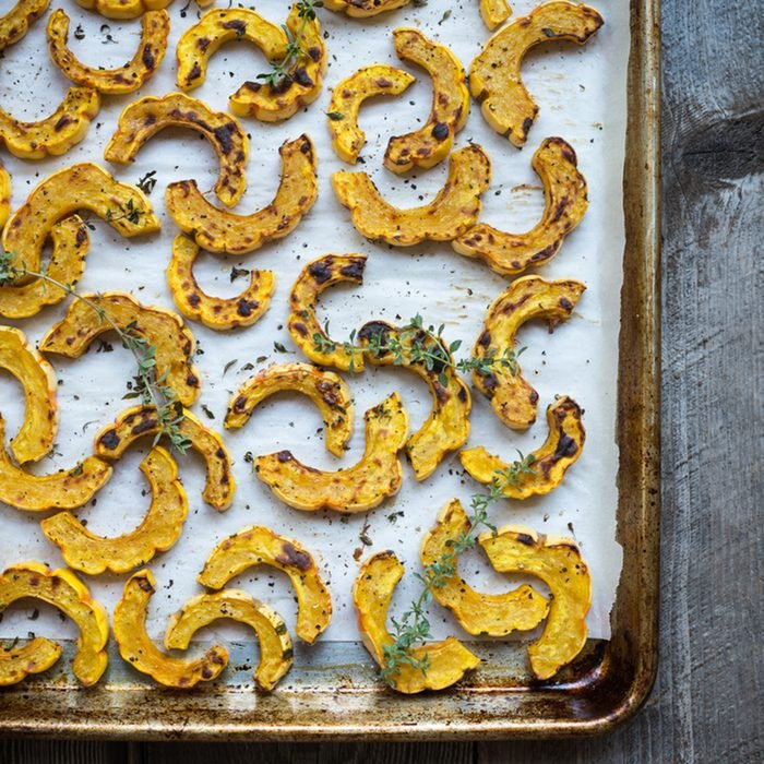 Sheet pan with freshly roasted delicata squash on parchment
