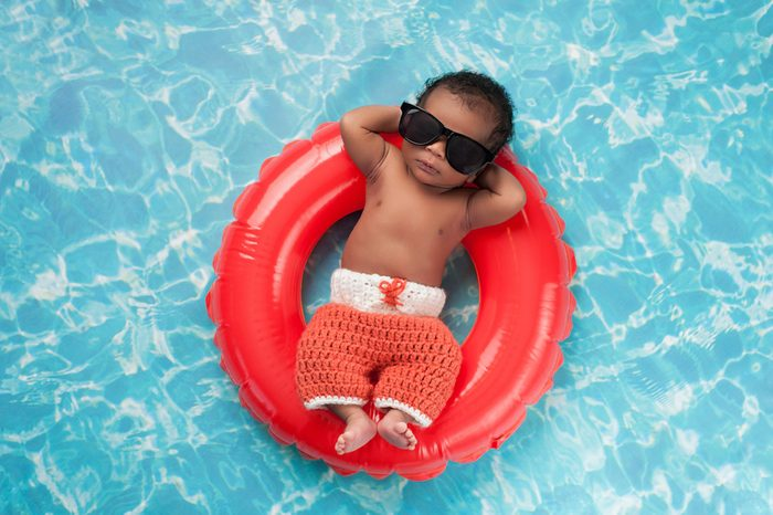 Two week old newborn baby boy sleeping on a tiny inflatable swim ring. He is wearing crocheted board shorts and black sunglasses.