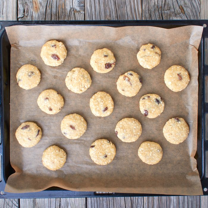 Uncooked oatmeal cookies on baking paper on a baking sheet