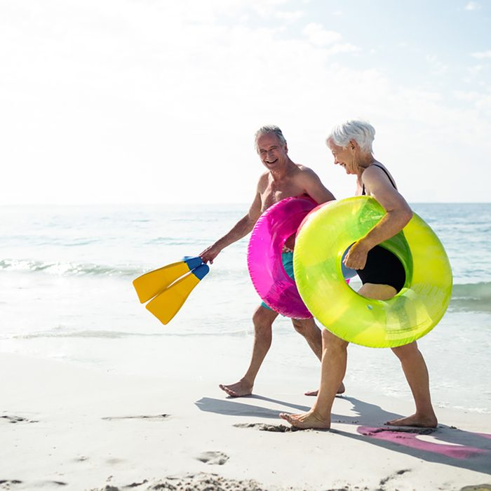 Happy senior couple walking on beach with inflatable rings and flippers on a sunny day; Shutterstock ID 398324230