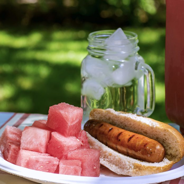 Picnic with Brats, Watermelon, and Ice Water in a Red Cooler in the Shade; Shutterstock ID 411394444