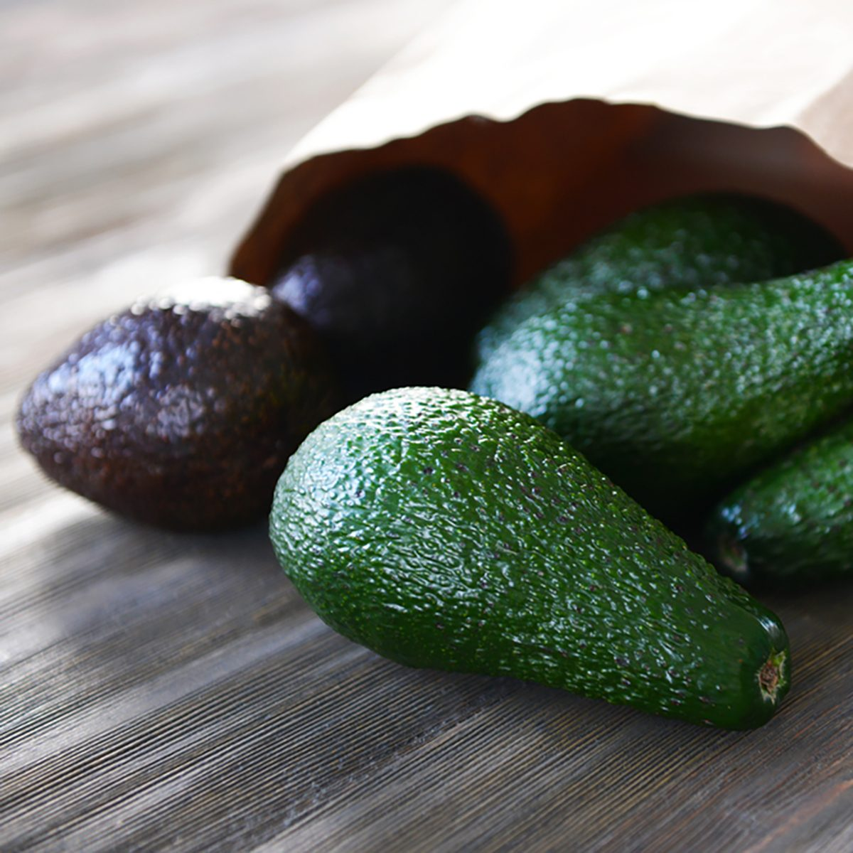 Fresh avocados in paper bag on wooden background;