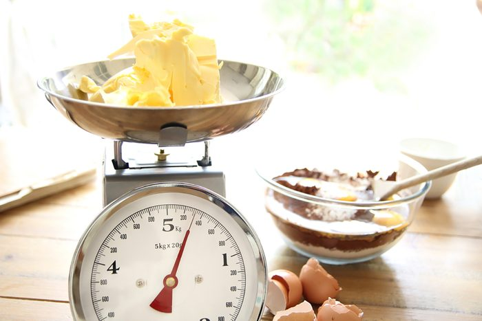 Butter being weighed for a chocolate cake; Shutterstock ID 434129020